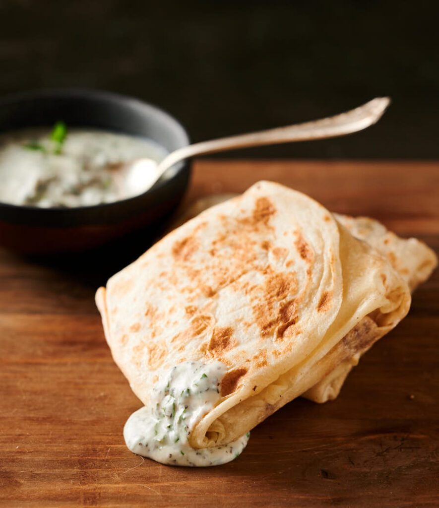 Mutton roti drizzled with mint raita.