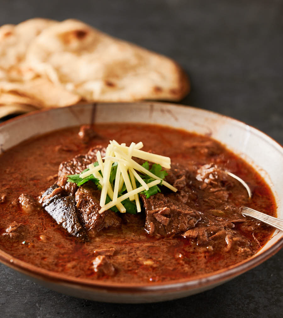 Bowl of nihari gosht with spoon ready to eat.