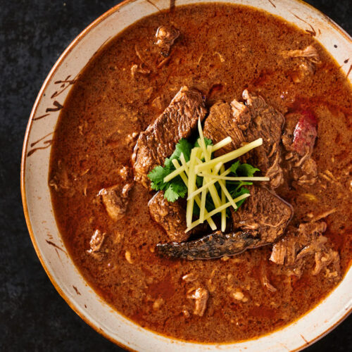 Serving bowl of nihari masala garnished with ginger and cilantro.
