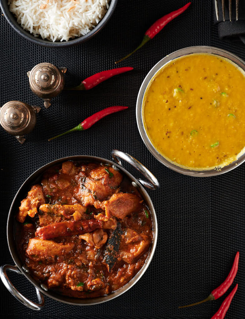 Bowls of chicken bhuna, dhal and rice from above.