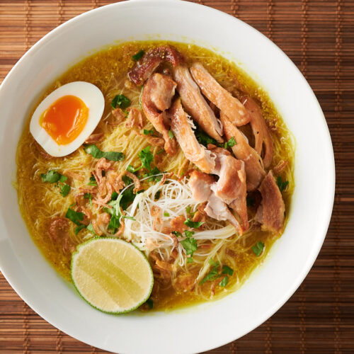 Bowl of soto ayam on bamboo background from above.
