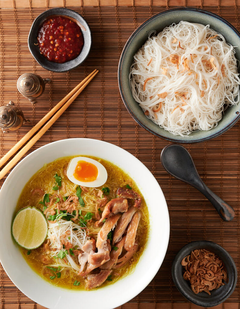Table scene with soto ayam, rice noodles, dried shallots and sambal oelek.