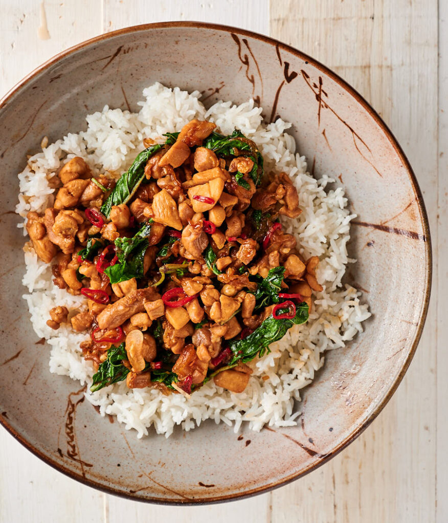 Bowl of Thai basil chicken on a bed of rice.