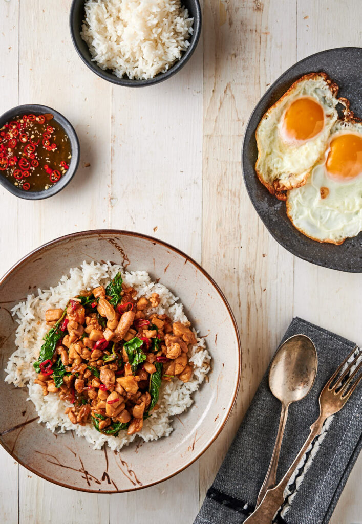 Thai basil chicken table scene - with rice, fried egg and nam prik plate