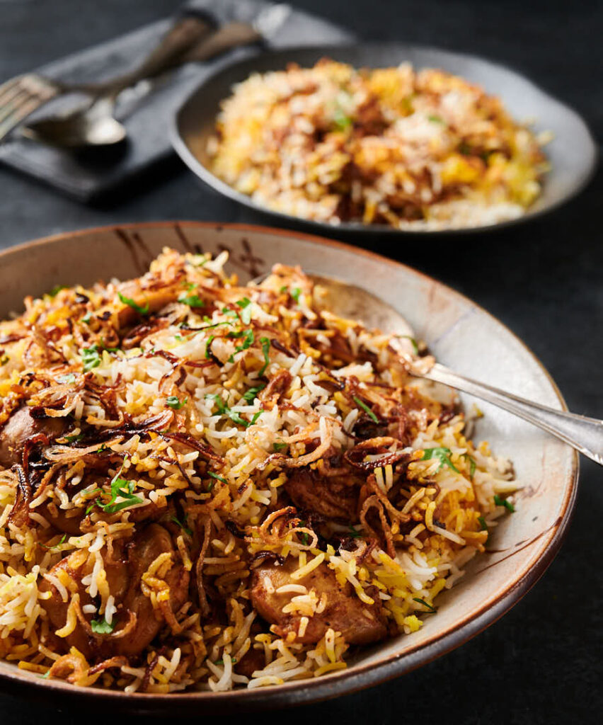 Chicken biryani in a bowl with serving spoon from the front.