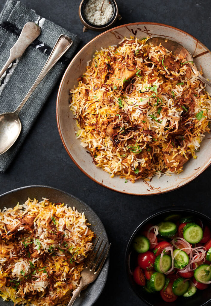 Chicken biryani table scene. Serving dish and plate of biryani from above.