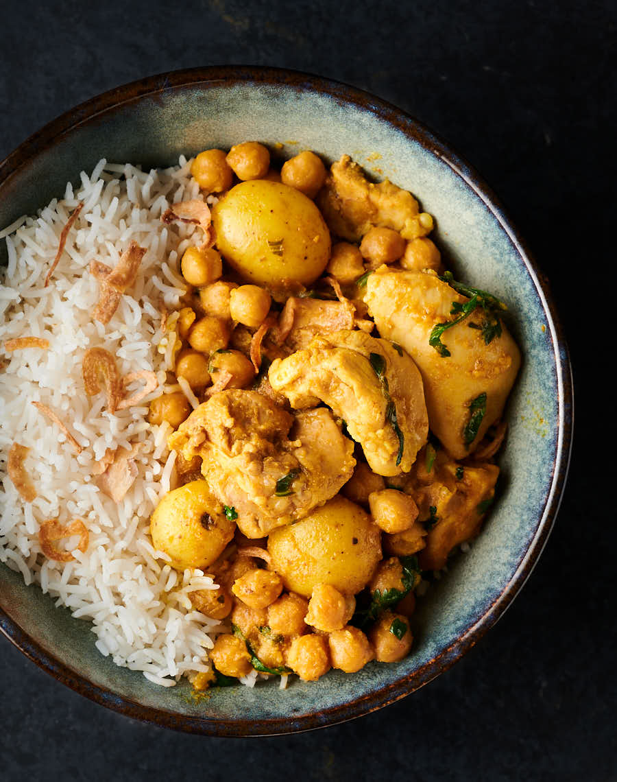 Bowl of chickpea and chicken curry with rice from above.