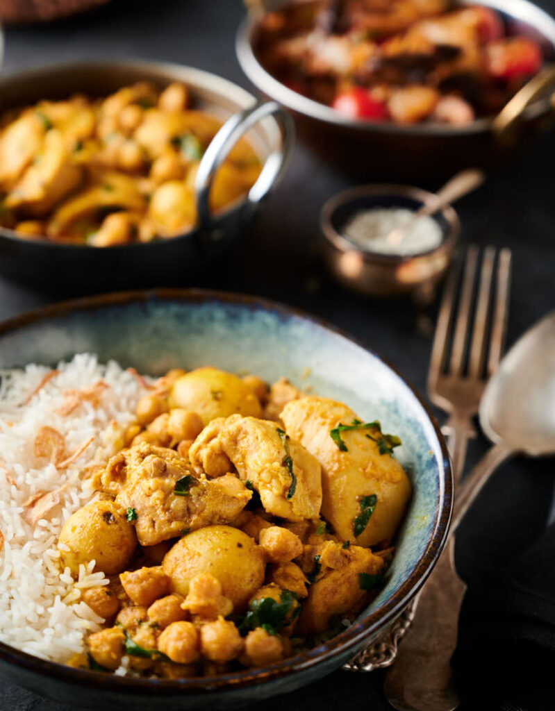 Chicken and chickpea curry in a bowl with rice from the front.