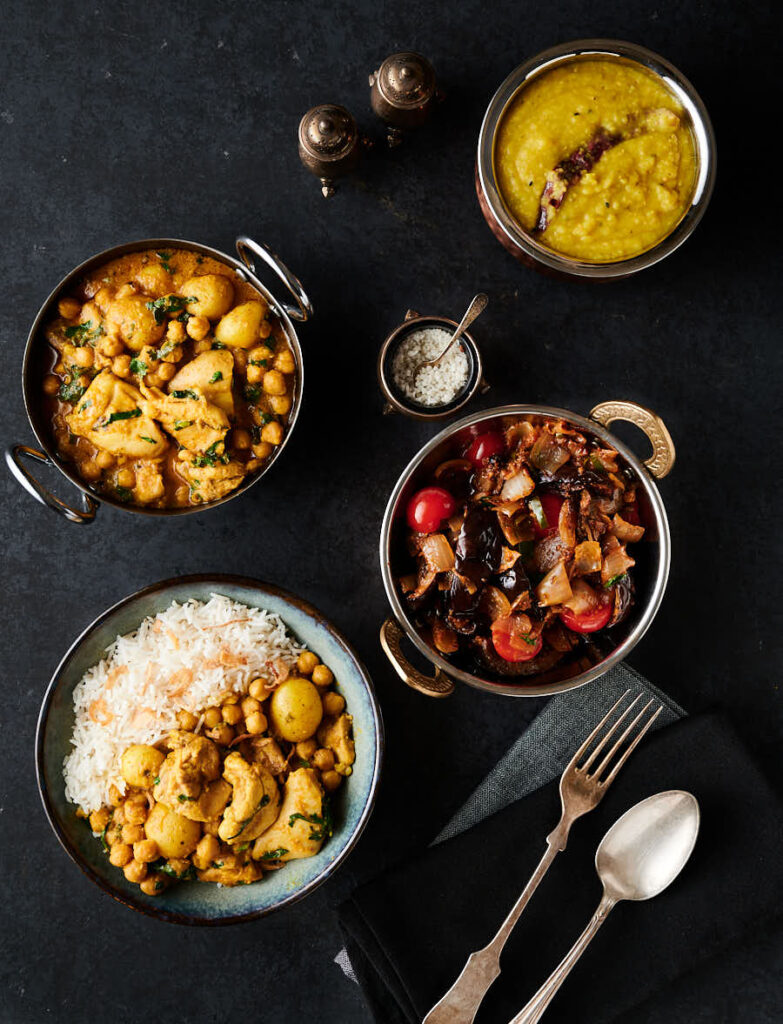 Table scene - chicken and chickpea curry, eggplant curry and dal from above.
