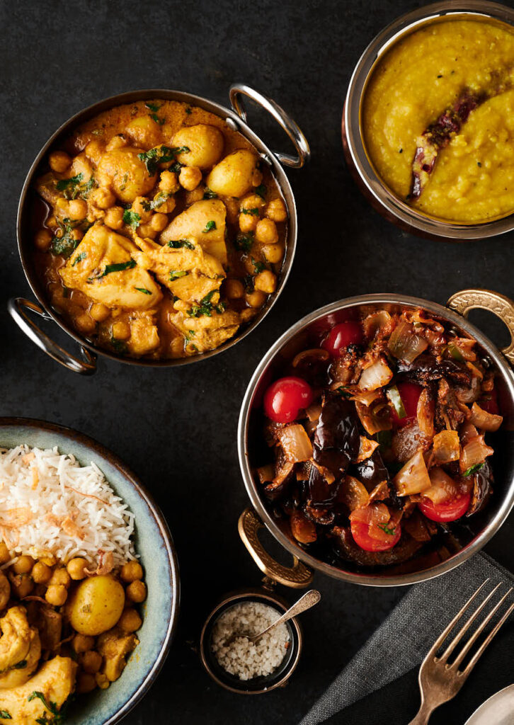 Chicken and chickpea curry and eggplant curry in serving bowls from above.