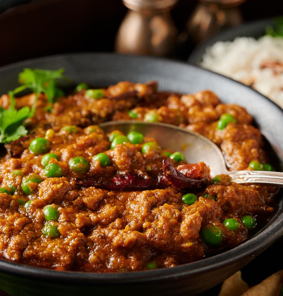 Close-up of keema matar with a spoon from the front.