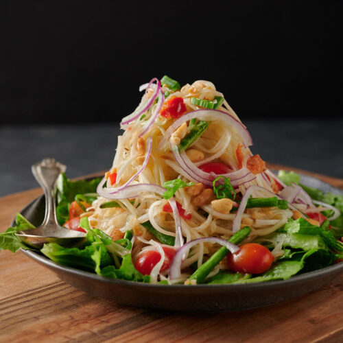 Mountain of som tam - papaya salad on a bed of greens from the front.