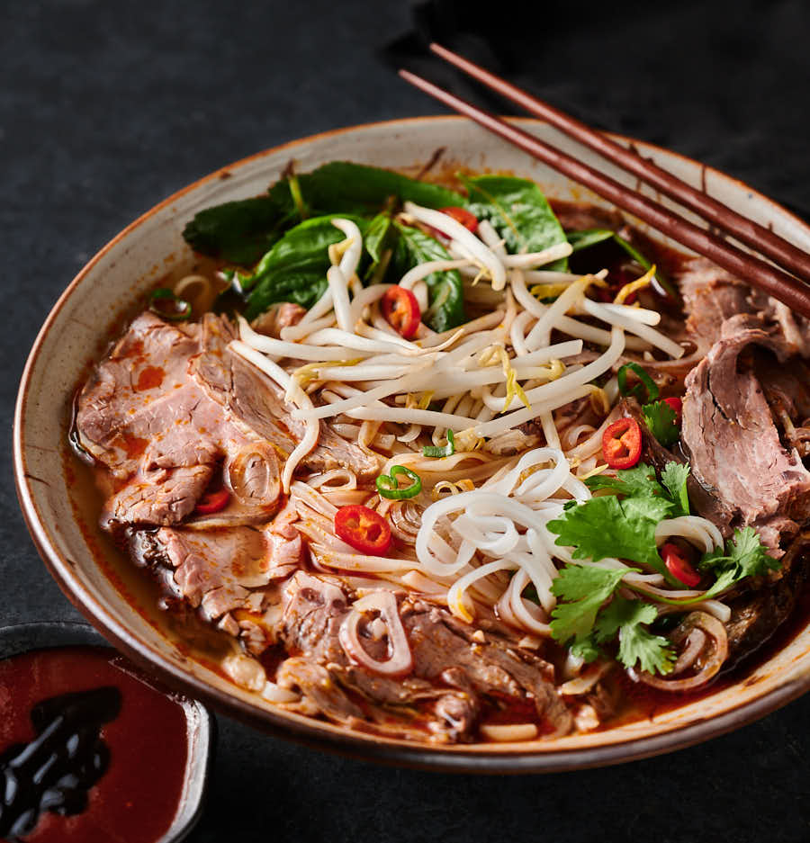 Spicy beef noodle soup in a bowl with chopsticks from the front.