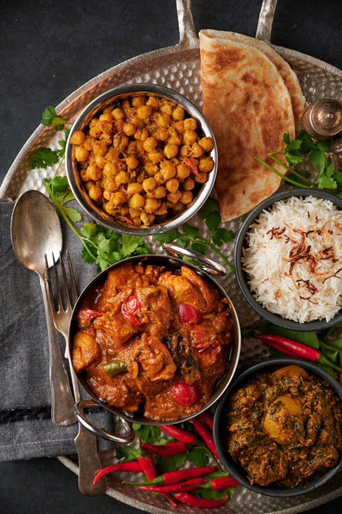 Garlic chilli chicken table scene with parathas, rice, chana and saag aloo from above.