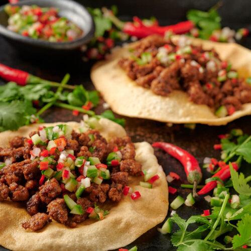 Two keema papadum and a bowl of kachumber salsa.
