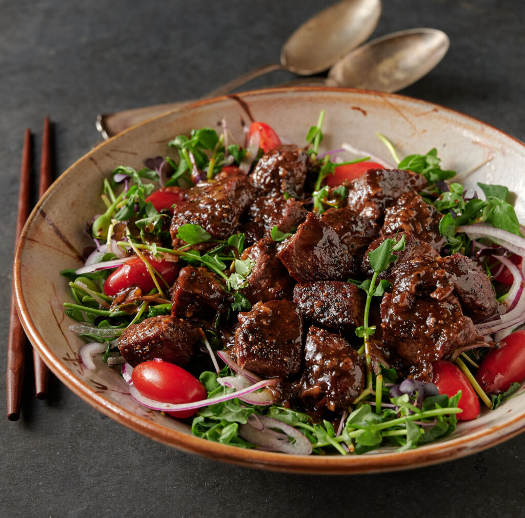 Bowl of shaking beef salad in a low round bowl from the front.