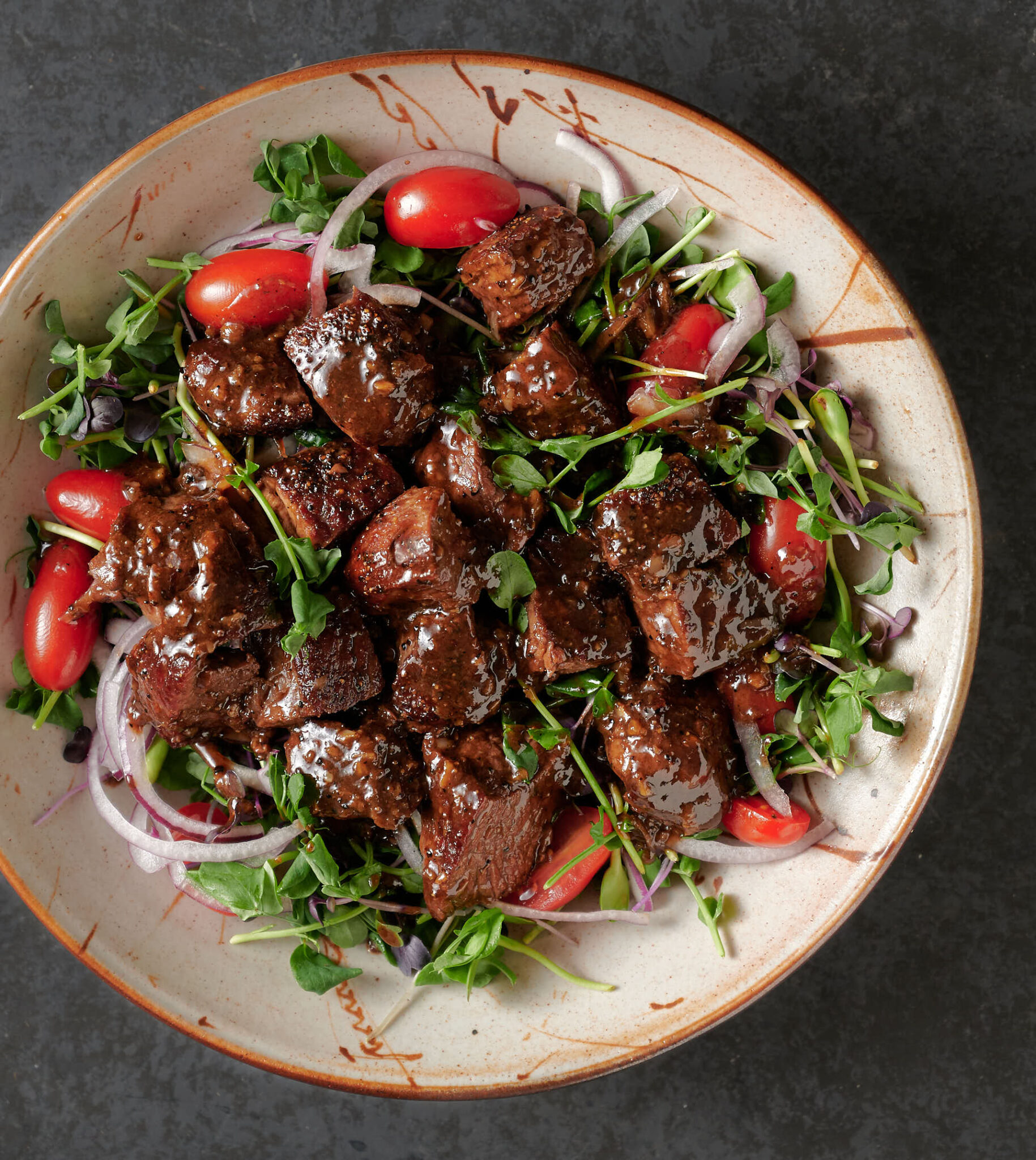 Bowl of shaking beef on a bed of micro-greens from above.