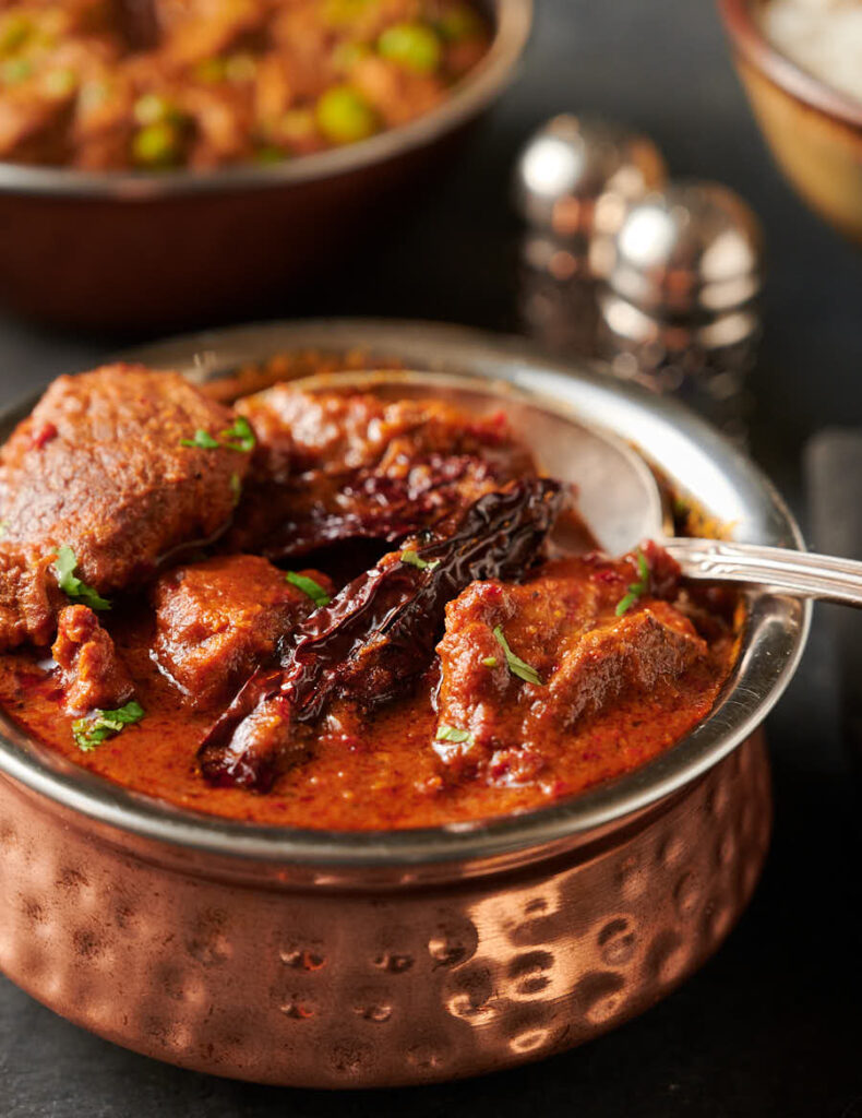 Close-up of an Indian copper serving bowl full of lamb vindaloo with a spoon.