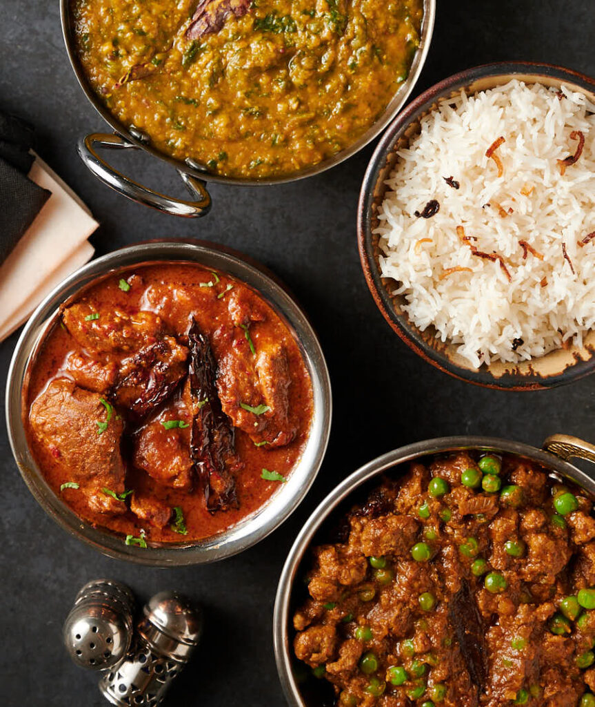 Lamb vindaloo, keema matar, dal palak and rice table scene from above.