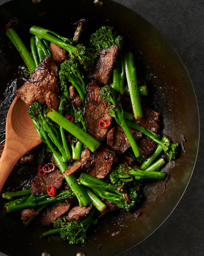 Wok full of Thai beef and broccoli with wooden spoon from above.
