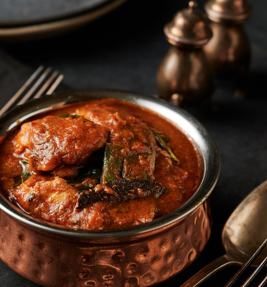Ceylon chicken in a Indian style hammered copper bowl from the front.
