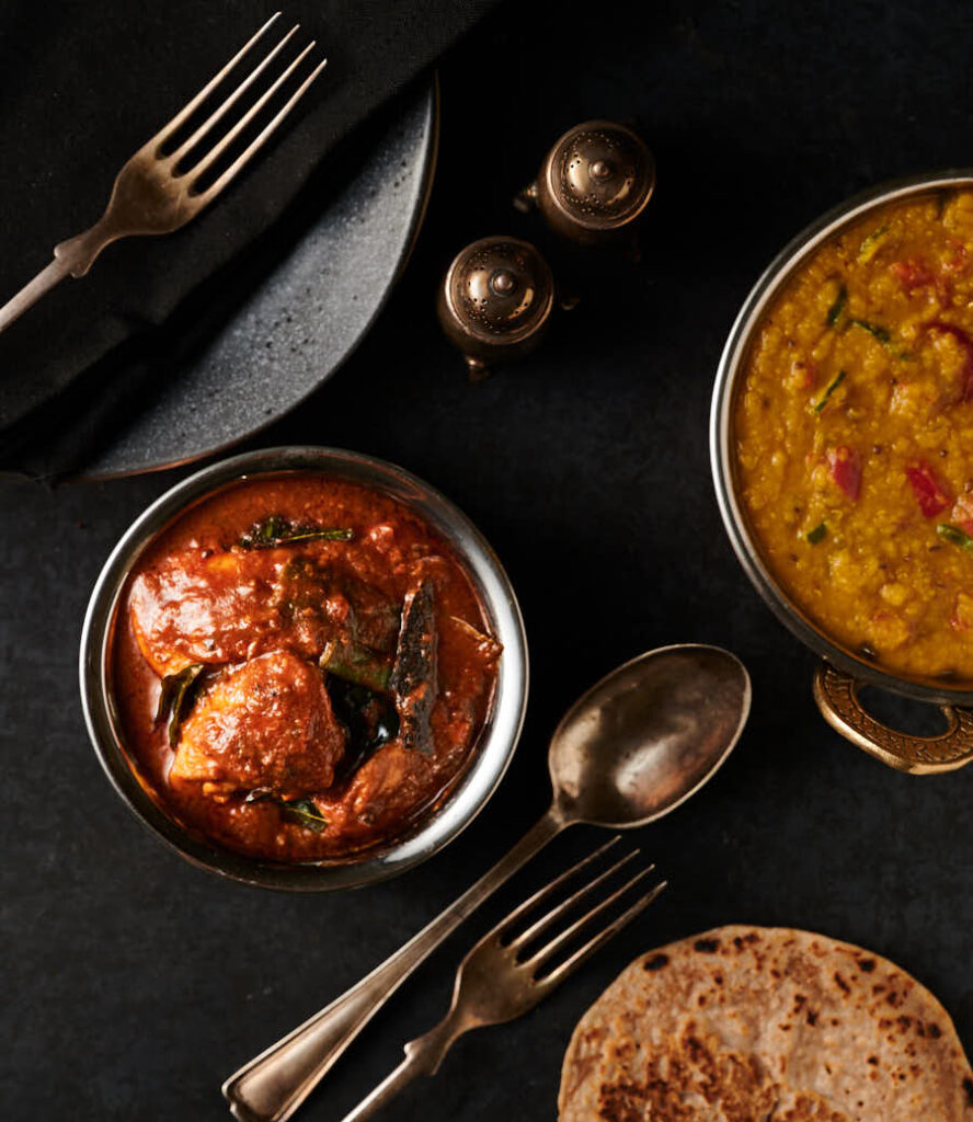 Table scene - Ceylon chicken curry, dal with tomato and green chili and chapatis from above.