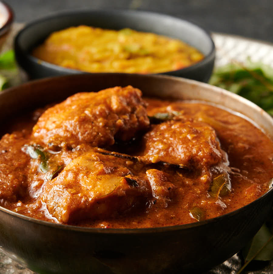 Closeup of chettinad chicken curry in a carbon steel bowl from the front.