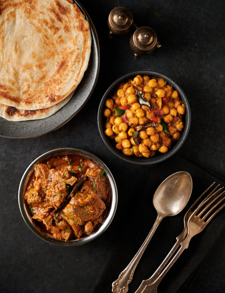 Table scene with Indian hotel style lamb madras, channa masala and parathas from above