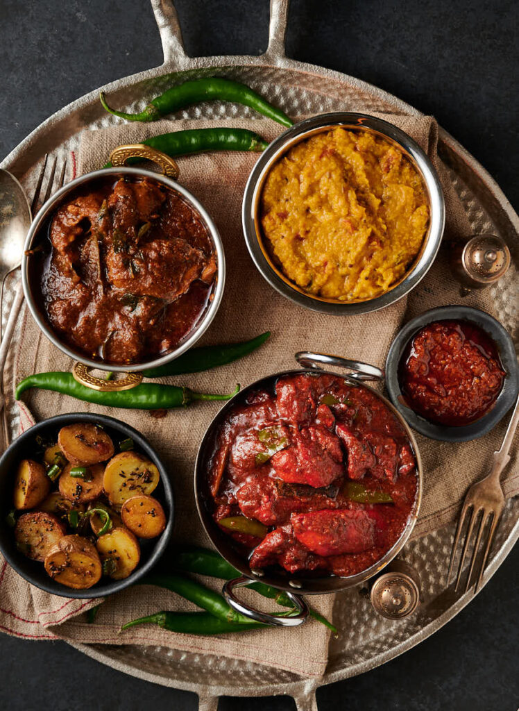 Naga chicken tikka curry, tarka dal, Ceylon chicken curry and chaat masala potatoes with green chilies.
