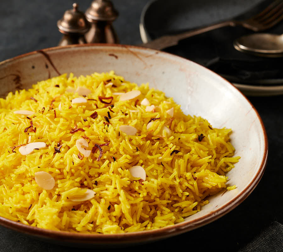 Bowl of indian restaurant style rice pilau from the front.