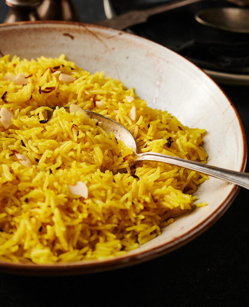 Bowl of indian restaurant style rice pilau with spoon from the front.