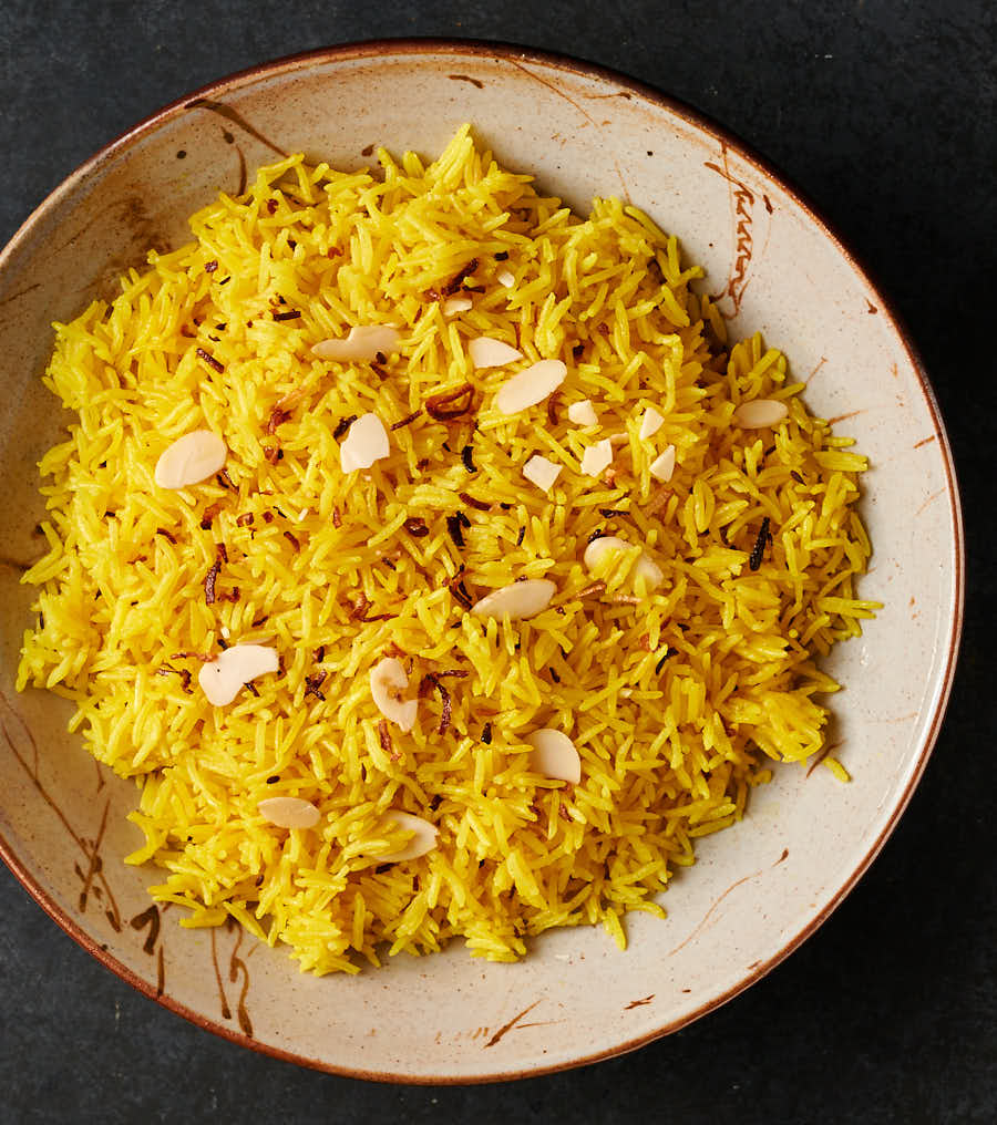 Bowl of turmeric coloured Indian restaurant style rice pilau from above.