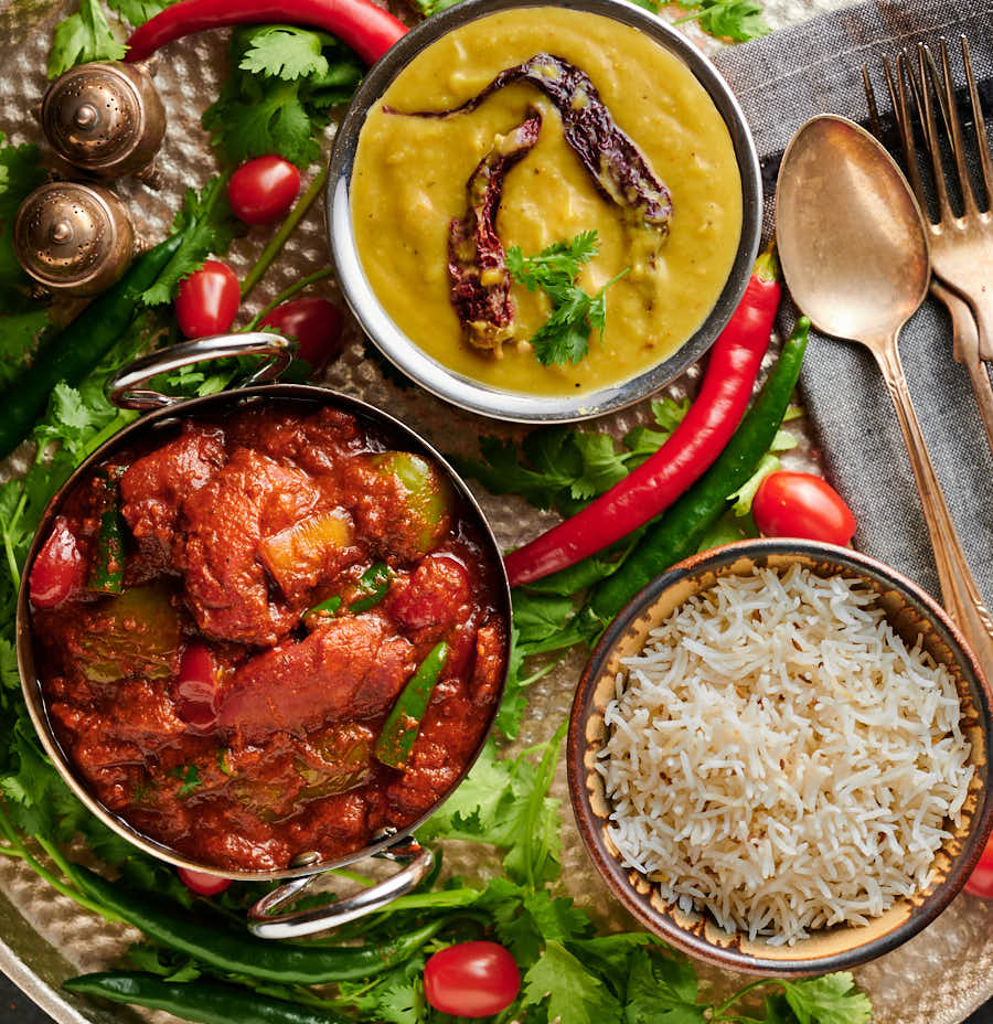 Table scene with chicken tikka jalfrezi, dal and rice from above.