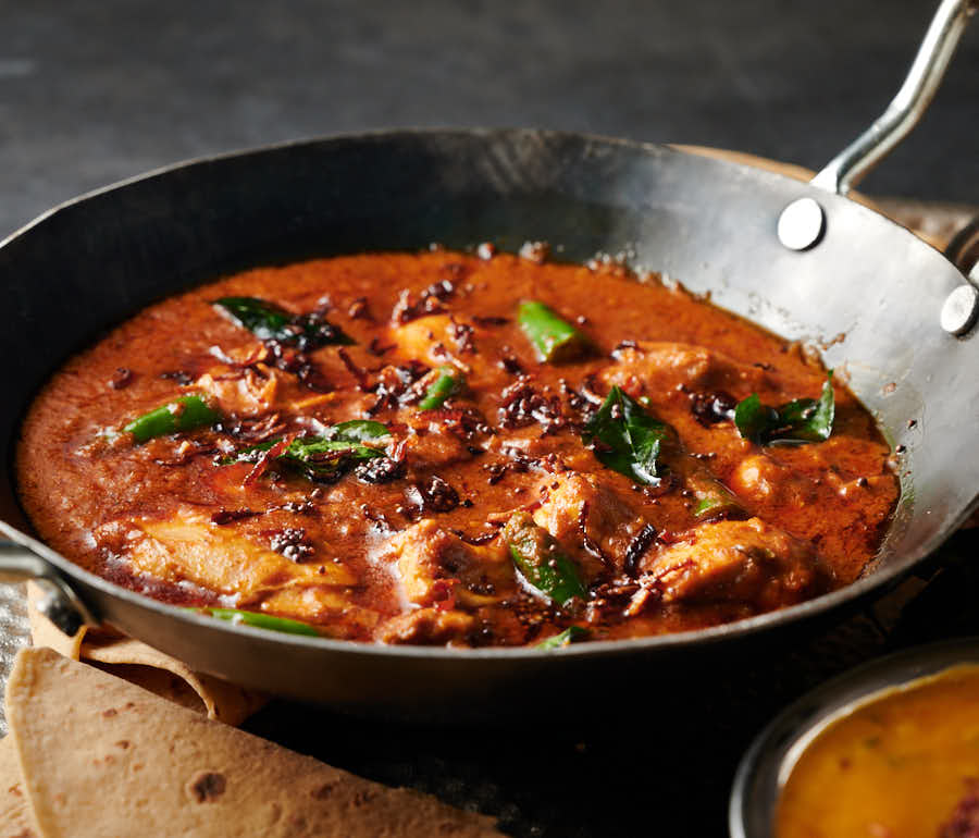Garnished Kerala chicken curry in a Balti bowl from the front