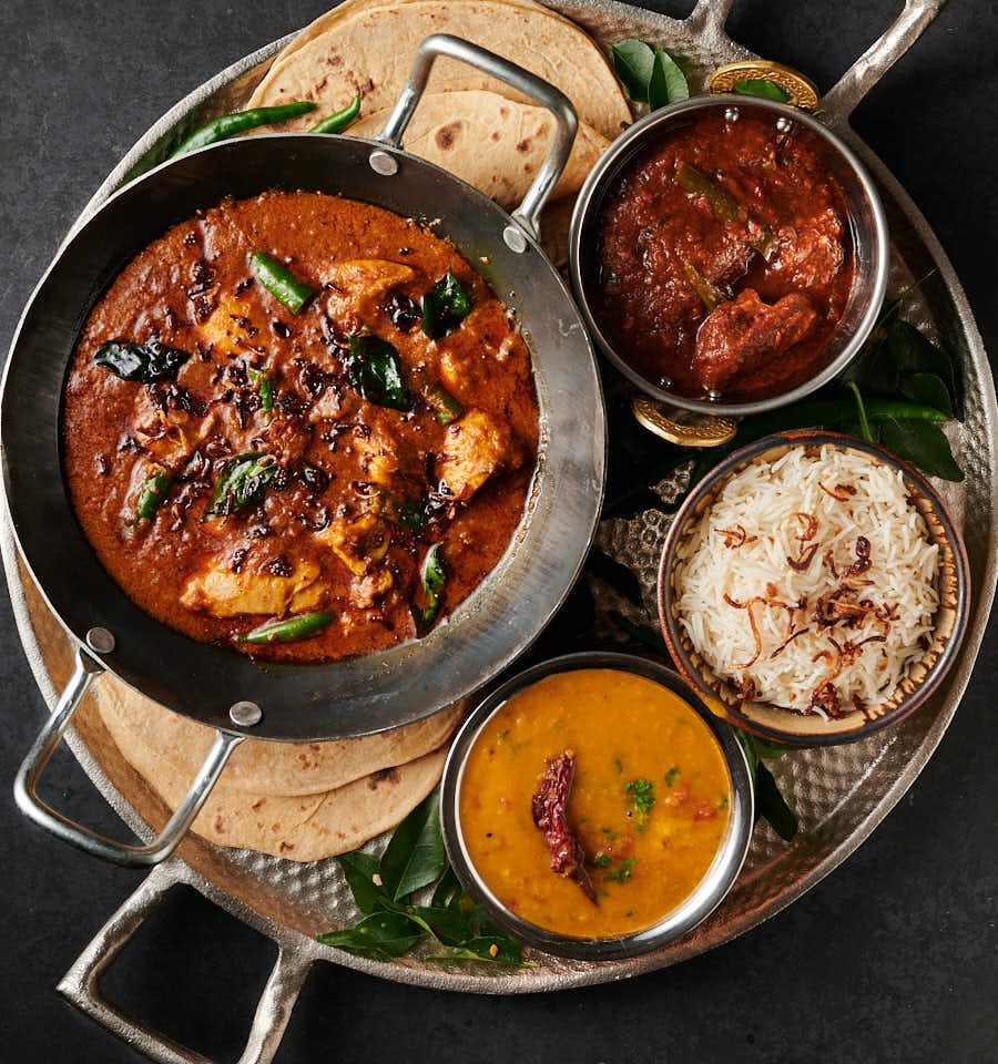 Table scene of hotel style Kerala chicken curry with rice, dal and chapatis.