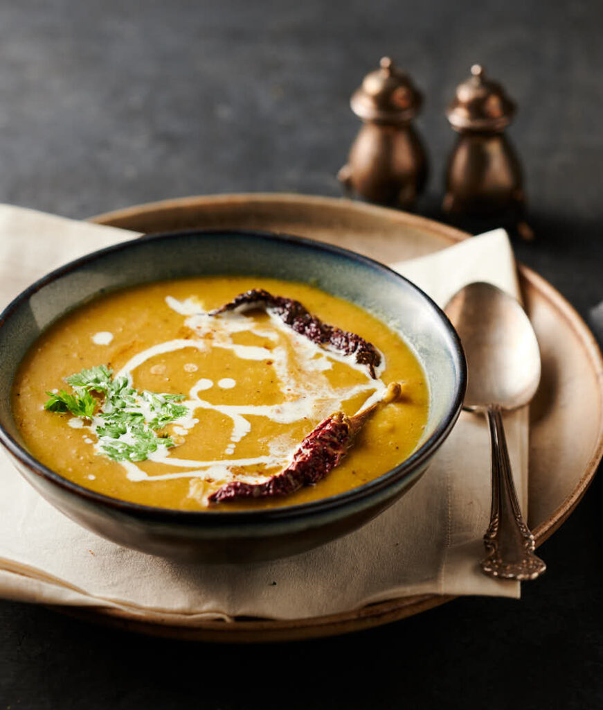 Bowl of mulligatawny soup garnished with drizzled cream, cilatntro and whole kashmiri chilies from the front.
