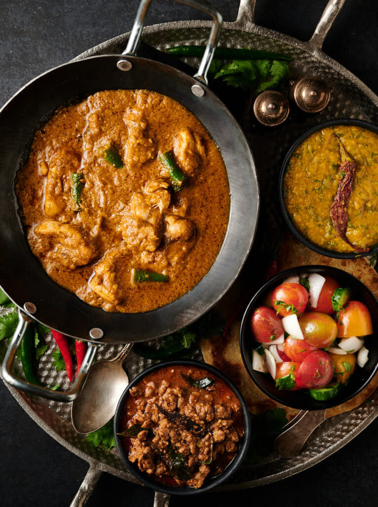 Hariyali chicken curry table scene with bowls of dal, nadan keema and kachumber.