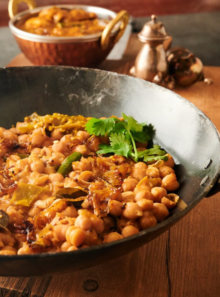 Serving bowl of green chili chana achari from the front.