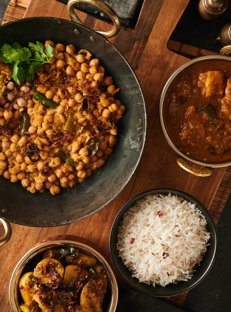 Table scene with serving bowls containing green chili chana achari, devilled potatoes, chicken dopiaza and rice from above.