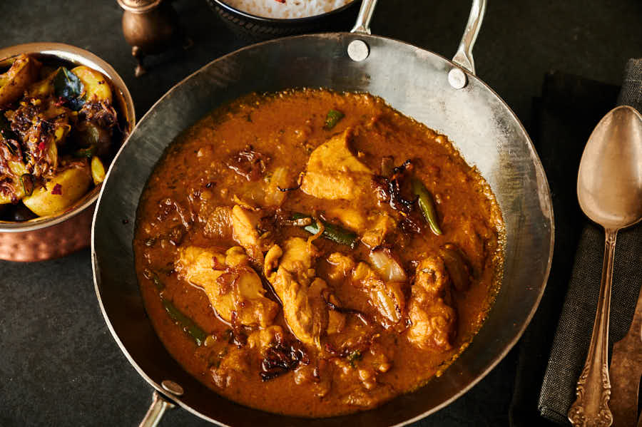Chicken dopiaza in a carbon steel karai table view.