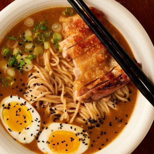 Closeup of bowl of curry chicken ramen garnished with black sesame seeds from above.