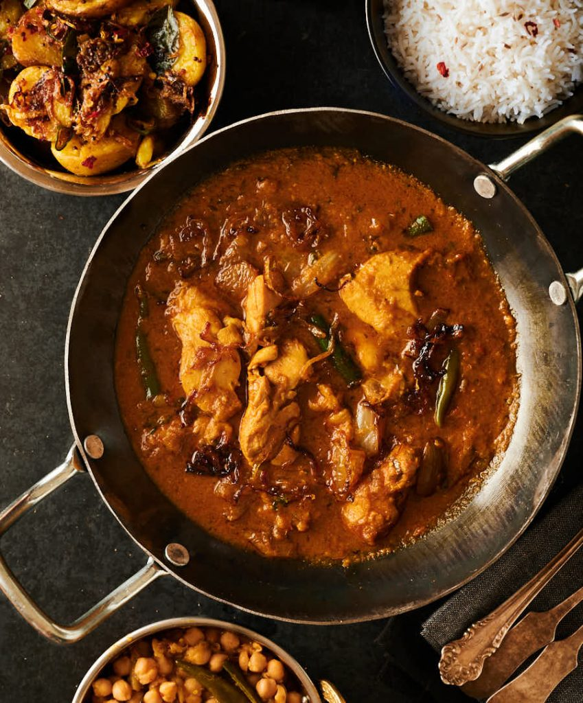 Indian hotel style chicken dopiaza with side dishes.