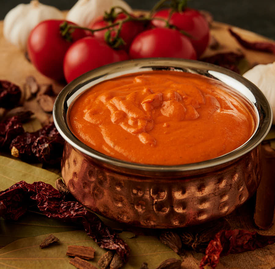 Bowl of makhani gravy in a hammered copper bowl from the front.