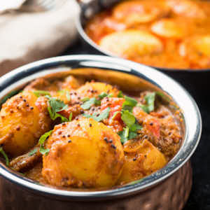 bombay potatoes in a copper bowl from the front