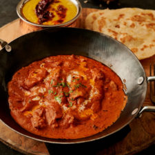 Hotel style butter chicken with parotha in a kadai from the front.