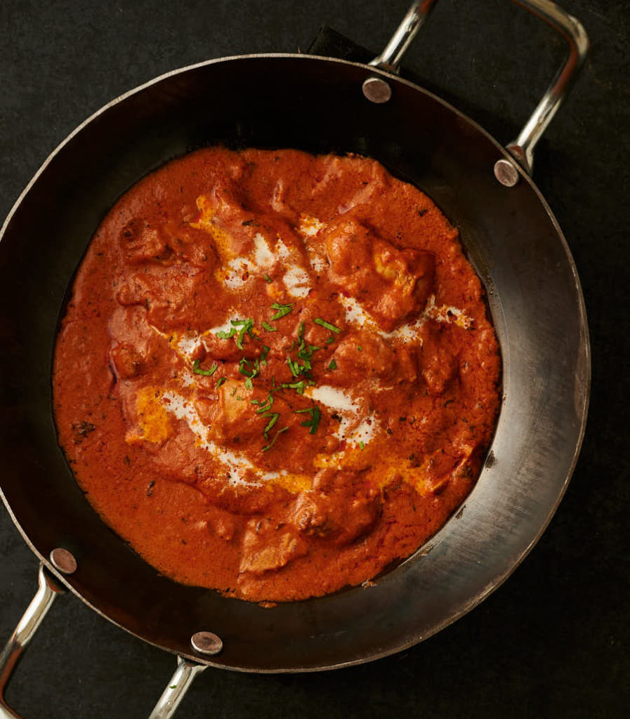 Hotel style butter chicken in a kadai from above.