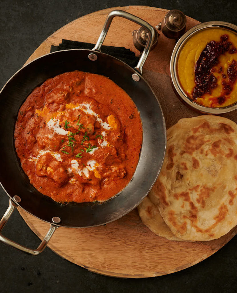 Butter chicken in a kadai table scene with paratha and tarka dal from above.