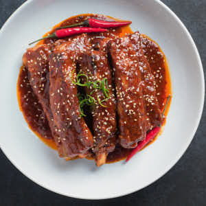 korean pork ribs garnished with white sesame seeds from above.