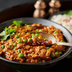 Bowl of keema matar with spoon
