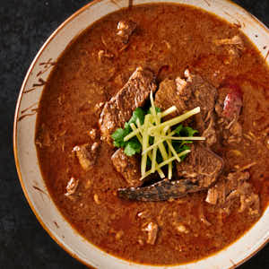 nihari gosht garnished with ginger in a bowl